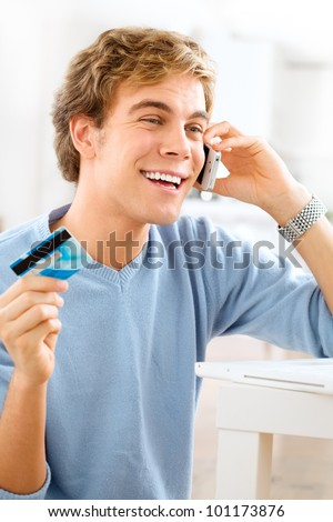 happy young student shopping on-line using credit card at home - stock photo