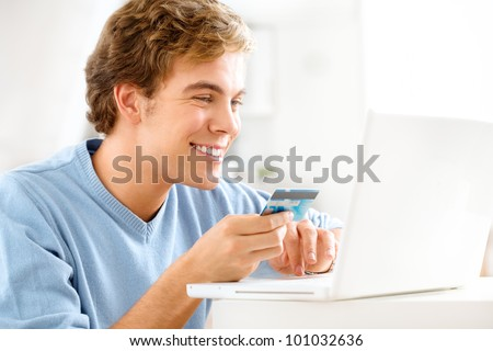 happy young student shopping online using credit card at home - stock photo