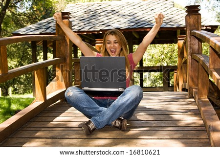 Happy young student using laptop outdoor. - stock photo