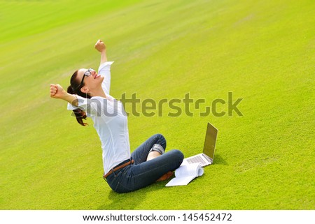 happy young student woman with laptop in city park study - stock photo