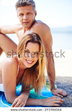 Happy young sunbather in bikini looking at camera with restful man on background - stock photo