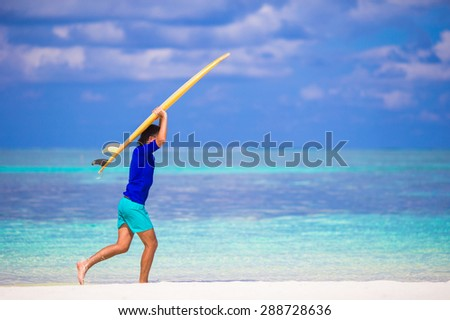 Happy young surf man at white beach with yellow surfboard - stock photo