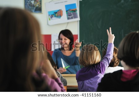happy young teacher woman at elementary school teaching and giving leassons to group of young smart children - stock photo