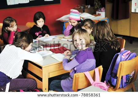 happy young teacher woman at elementrary school teaching and giving leassons to group of young smart children - stock photo