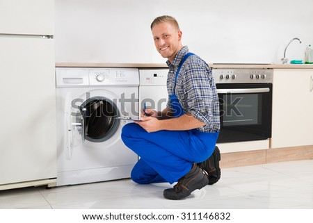 Happy Young Technician Writing On Clipboard In Kitchen - stock photo