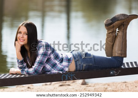 Happy young teen girl posing in a blue flannel shirt and jeans with boots - stock photo