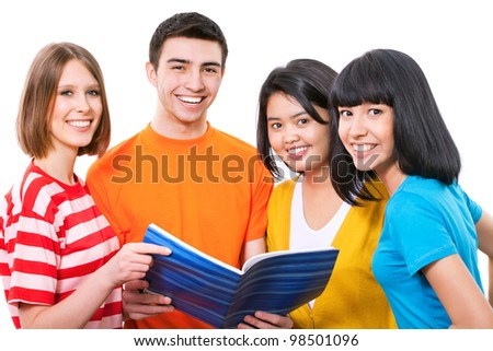 Happy young teenager students standing and smiling with book - stock photo