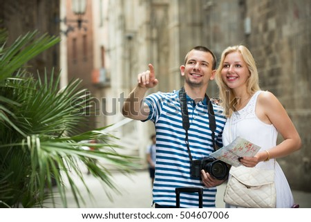 Happy young tourist couple sightseeing city with map and taking pictures on professional camera