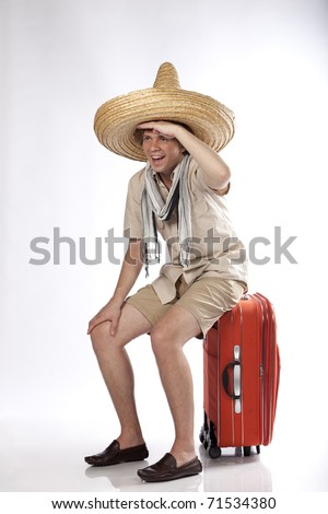 Happy young tourist looking away while he is sitting on his luggage - stock photo