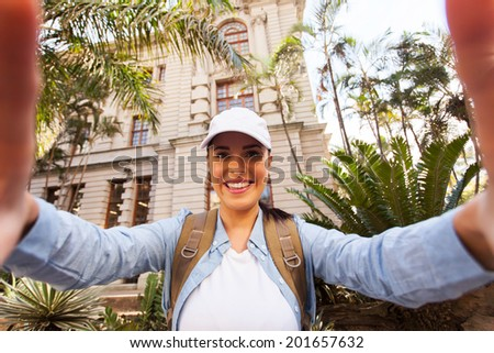 happy young tourist taking a selfie in front of an old building  - stock photo