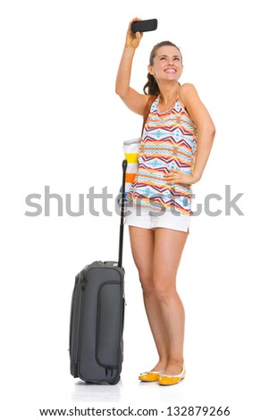 Happy young tourist woman with wheel bag taking self photo - stock photo