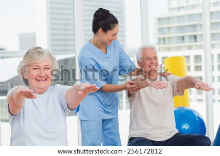 Happy young trainer assisting senior couple in exercising at gym - stock photo