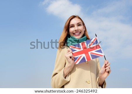 happy young travel woman holding British England flag with sky background, caucasian beauty
