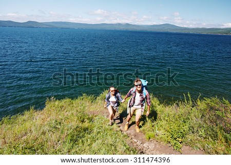 Happy young travelers hiking by the seaside