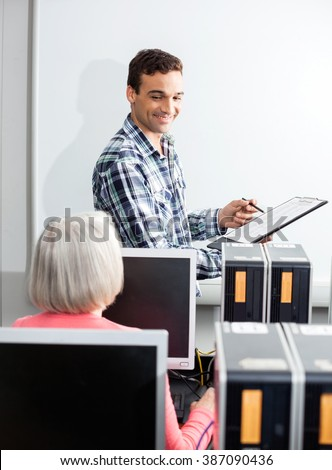 Happy Young Tutor Holding Clipboard In Computer Class