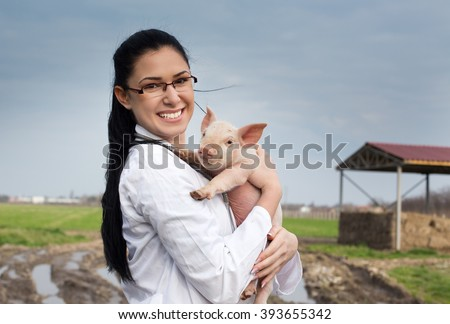 Happy young veterinarian girl holding cute piglet in her arms on the farm - stock photo