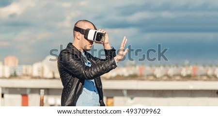 Happy young wearing a pair of VR glasses touching with his hands raised above the city on the rooftop building with the blue sky background excited by augmented reality