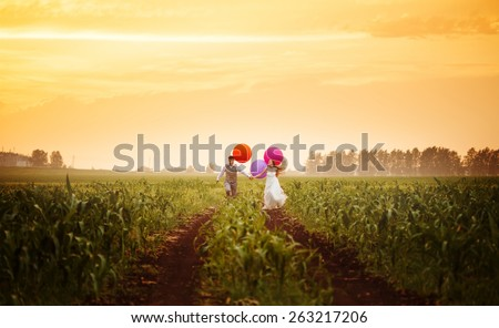 Happy young wedding couple running on the sunset field with big bright colorful balloons - stock photo