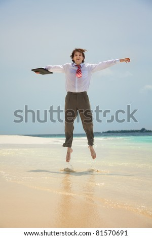 Happy young white-collar worker jumping on the shore of the sea - stock photo