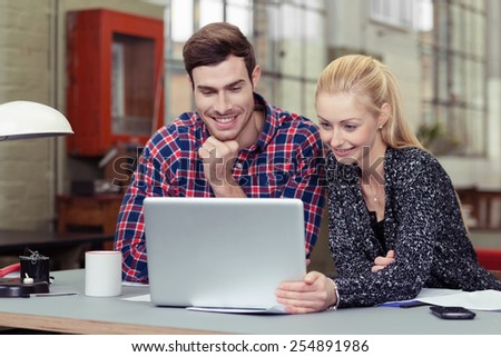 Happy Young White Couple Watching Something on Laptop Computer at the Desk. - stock photo