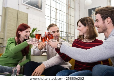 Happy Young White Friends in Casual Long Sleeve T-Shirts Tossing a Glass of Drink While Resting at Living Room - stock photo