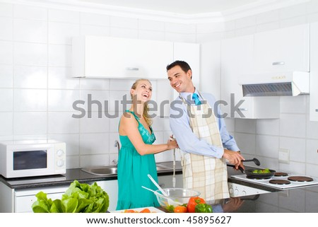happy young wife help husband tie up apron in kitchen - stock photo