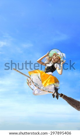 Happy young witch flying on a broom in carnival costume on a background of blue sky and white clouds - stock photo