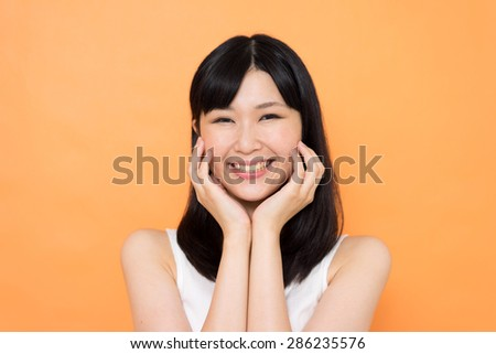 happy young woman against orange background - stock photo