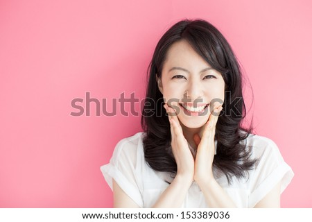happy young woman against pink background  - stock photo