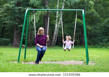 Happy young woman and a little baby girl swinging on a playground - stock photo
