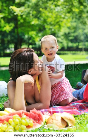 happy young woman and baby have fun while playing in beautiful bright park at summer season - stock photo