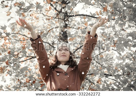 Happy young woman and falling snow with tree in background - stock photo