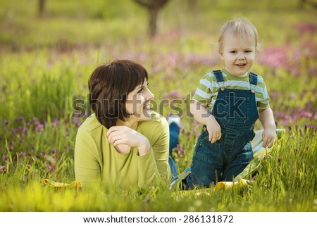 Happy young woman and her child talking and having rest in spring garden