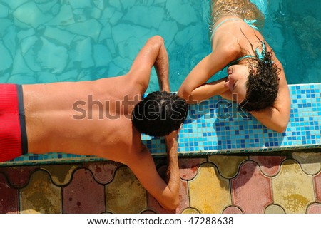 Happy young woman and man in water pool - stock photo
