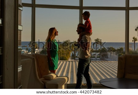Happy young woman and man with little boy look at each other close to window in sunset flares - stock photo