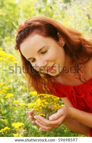 Happy young woman and wild flowers.