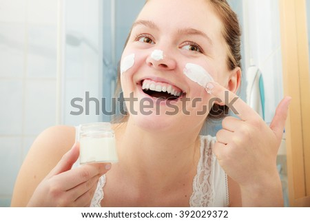 Happy young woman applying cleansing moisturizing skin cream on face. Girl taking care of dry complexion layering moisturizer. Skincare. - stock photo