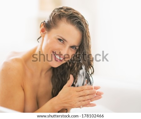 Happy young woman applying hair conditioner - stock photo