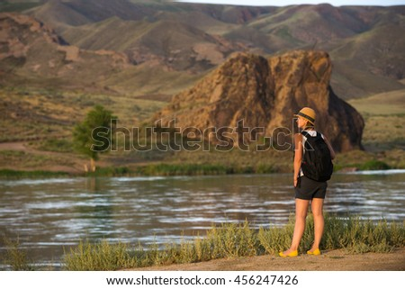 Happy young woman at beautiful view of Ili river canyon, travel in Kazakhstan