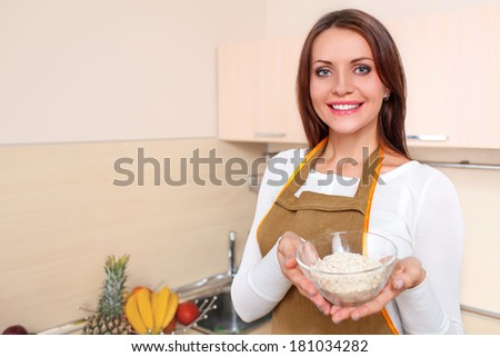 happy young woman at kitchen holding plate of oatmeal - stock photo