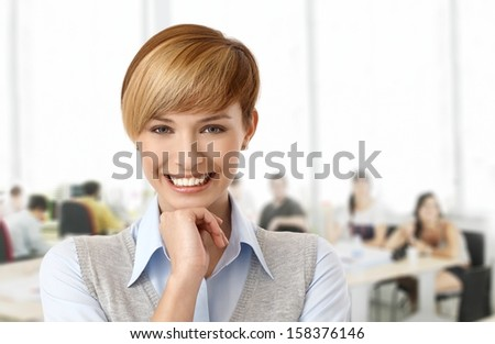 Happy young woman at office smiling. - stock photo