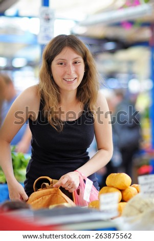 Happy young woman at the farmer market  - stock photo