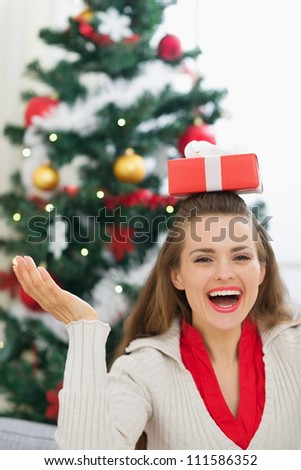 Happy young woman balancing Christmas present box on head - stock photo