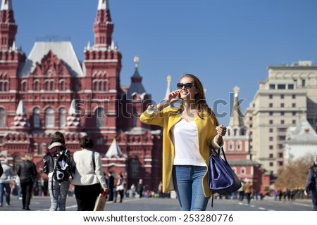 Happy young woman calling by phone in red square, Moscow, Russia - stock photo