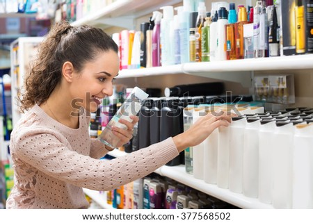 Happy young woman choosing hair conditioner and smiling