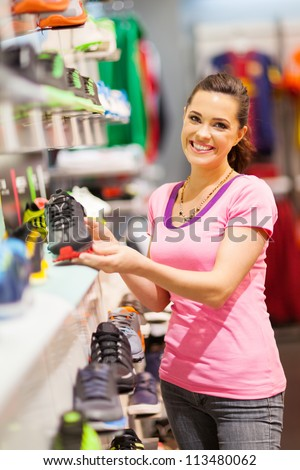 happy young woman choosing sports shoes to buy in store - stock photo