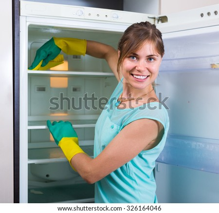 Happy young woman cleaning empty refrigerator in  kitchen - stock photo
