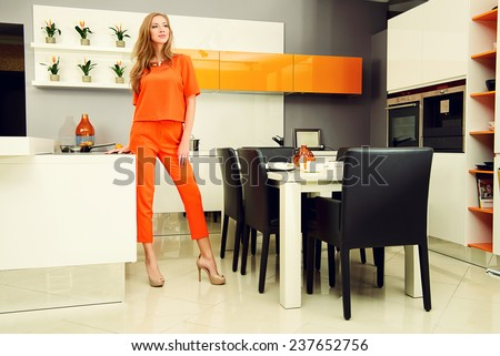 Happy young woman cooking in the kitchen at home. Healthy eating. Home interior. Furniture. - stock photo