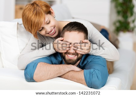 Happy young woman covering mans eyes while lying on sofa - stock photo