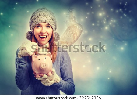Happy young woman depositing money into her pink piggy bank  - stock photo